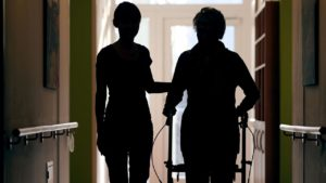 Younger woman holding older womans arm as they walk in the hospital hallway backlit