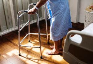 Elderly person in a walker standing in a hospital gown in their room