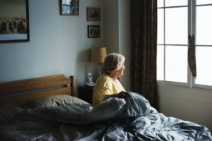Elderly woman getting out of bed looking out the window