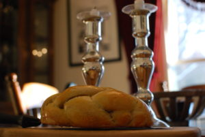 Shabbat challah and candlesticks on table